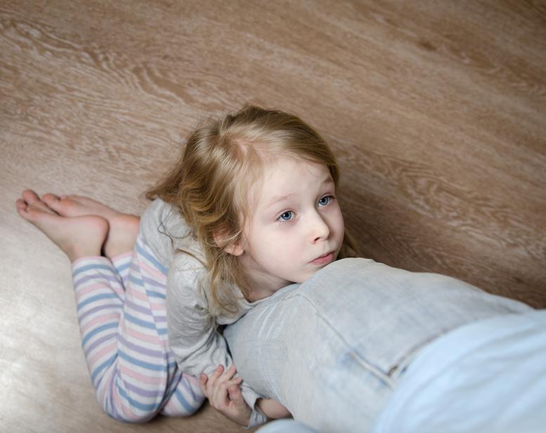 Little girl hugging dad's leg